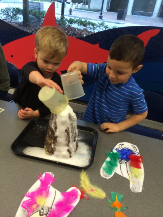 kids pour water into volcano model