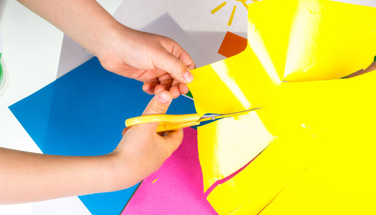 scissors cutting yellow paper