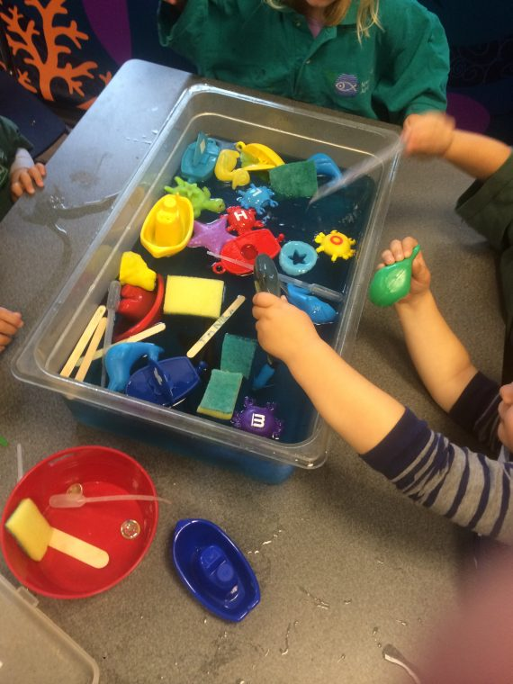 kid hands play with toys in water tub