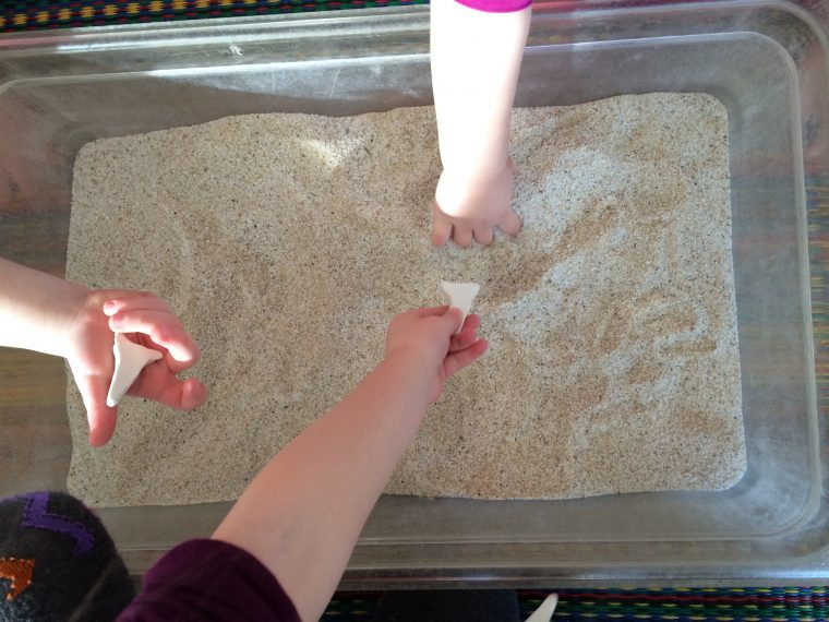 little hands in tub of sand