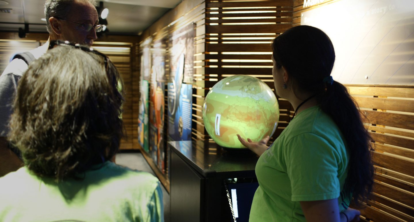 Aquarium educator talks with visitors next to globe