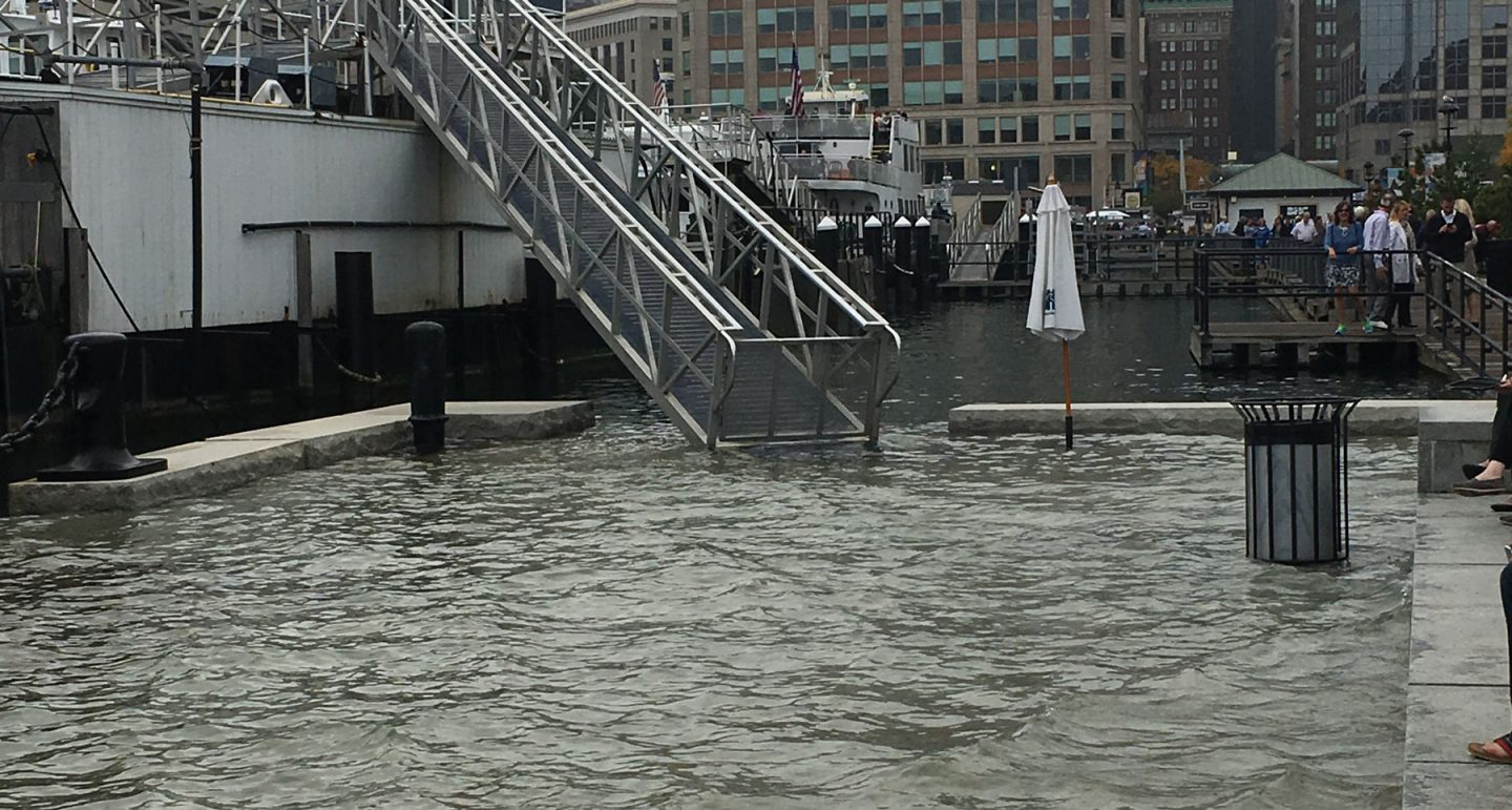 ship's gangplank leads down into a foot of water on Long Wharf