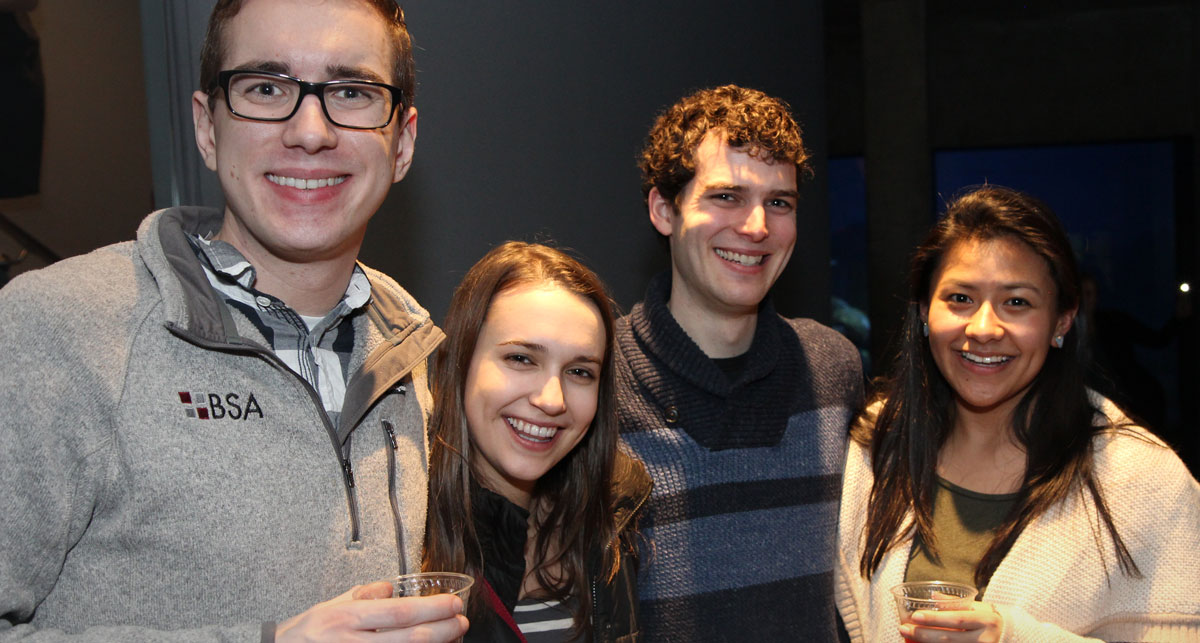 young adults smiling holding cocktails