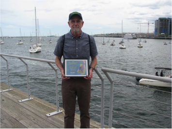 man stands next to harbor holding award