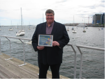 gilmore stands next to harbor holding award