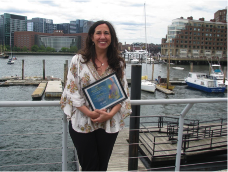woman stands next to harbor holding award