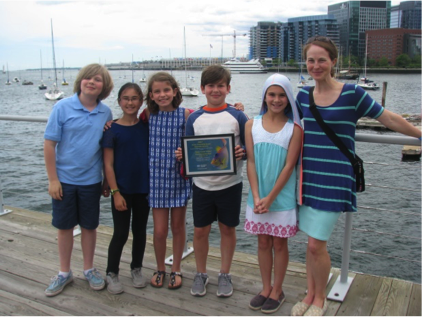 kids stand next to harbor holding award