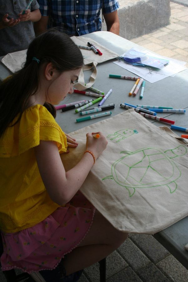 A World Oceans Day 2018 visitor decorates a tote bags in the members activity Make-A-Bag, Take-A-Bag.