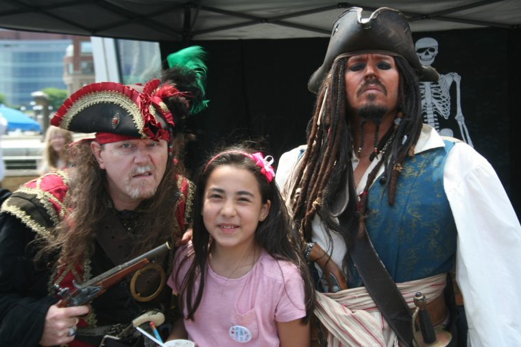 A World Oceans Day 2018 visitor poses with members of the Rogues Armada.