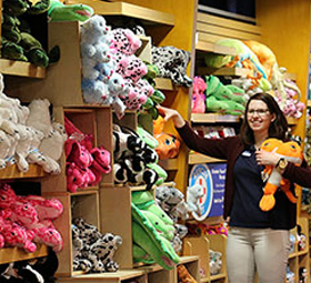 woman in gift shop holding plush