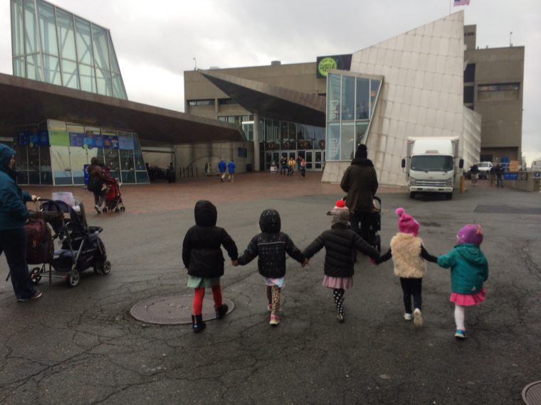 young children hold hands walking across Aquarium plaza