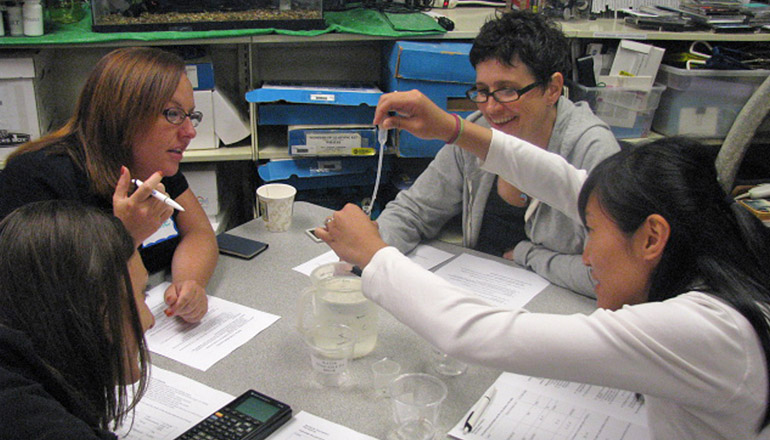 Teachers with test tube working at table