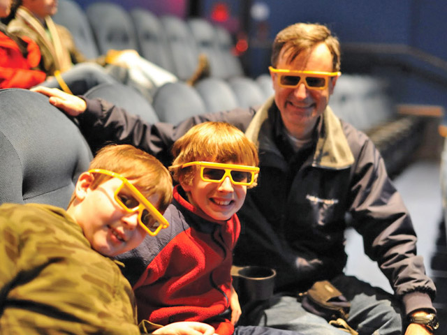 A family wearing IMAX glasses in the theater