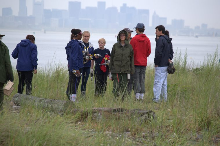 teens stand on sea grass with Boston skyline in background