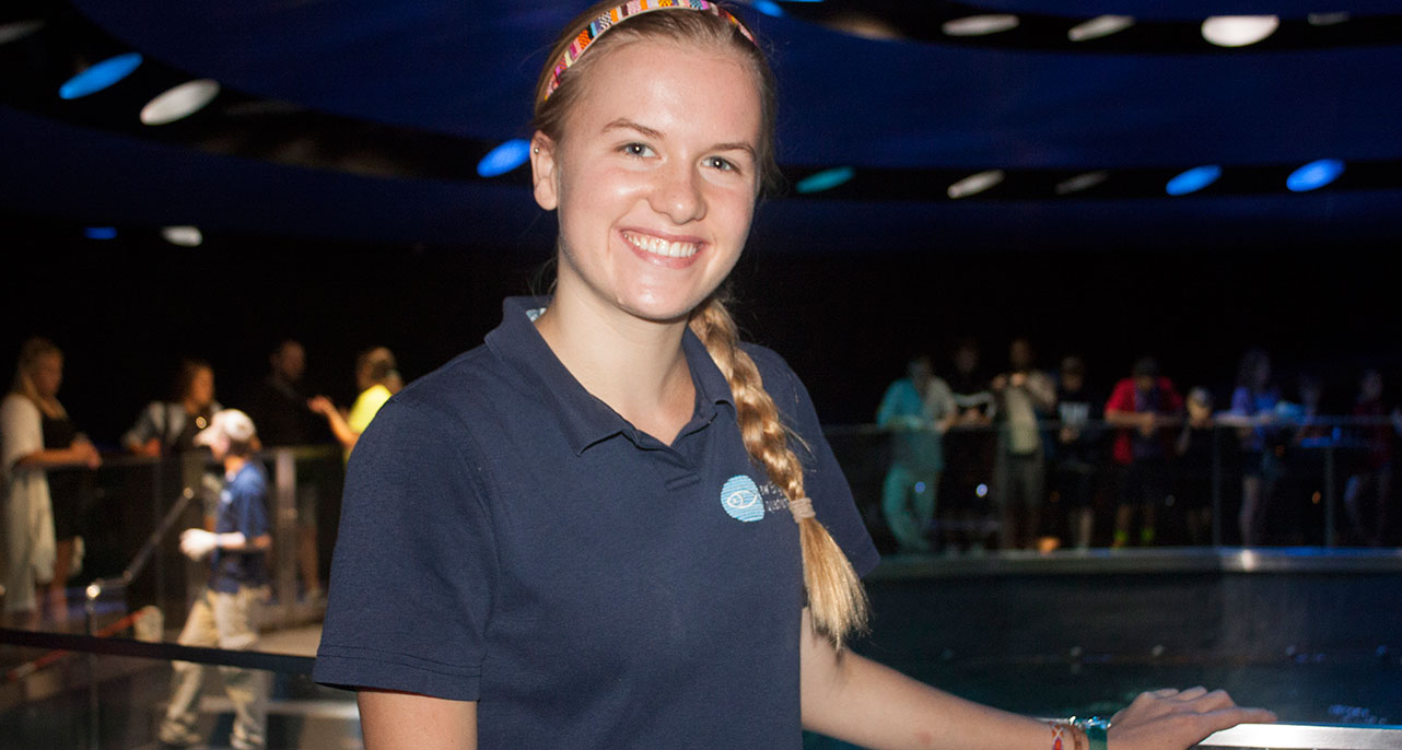intern smiles near giant ocean tank