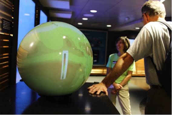 visitors learn about climate change with educators at the magic globe