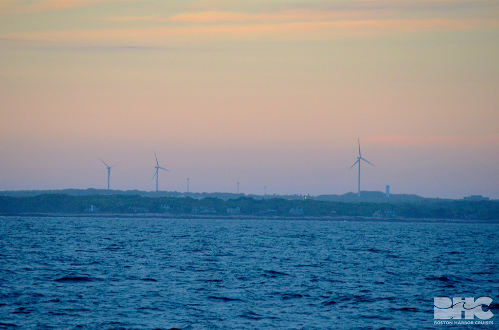 wind turbines against a sunset