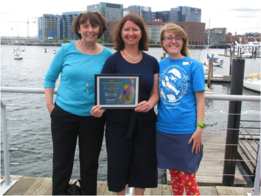 group stands next to harbor holding award