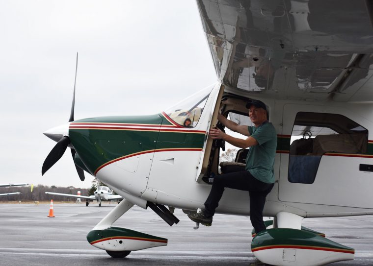 volunteer pilot climbs into plane
