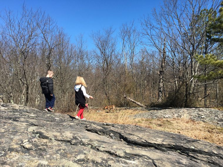 kids walk on large rock