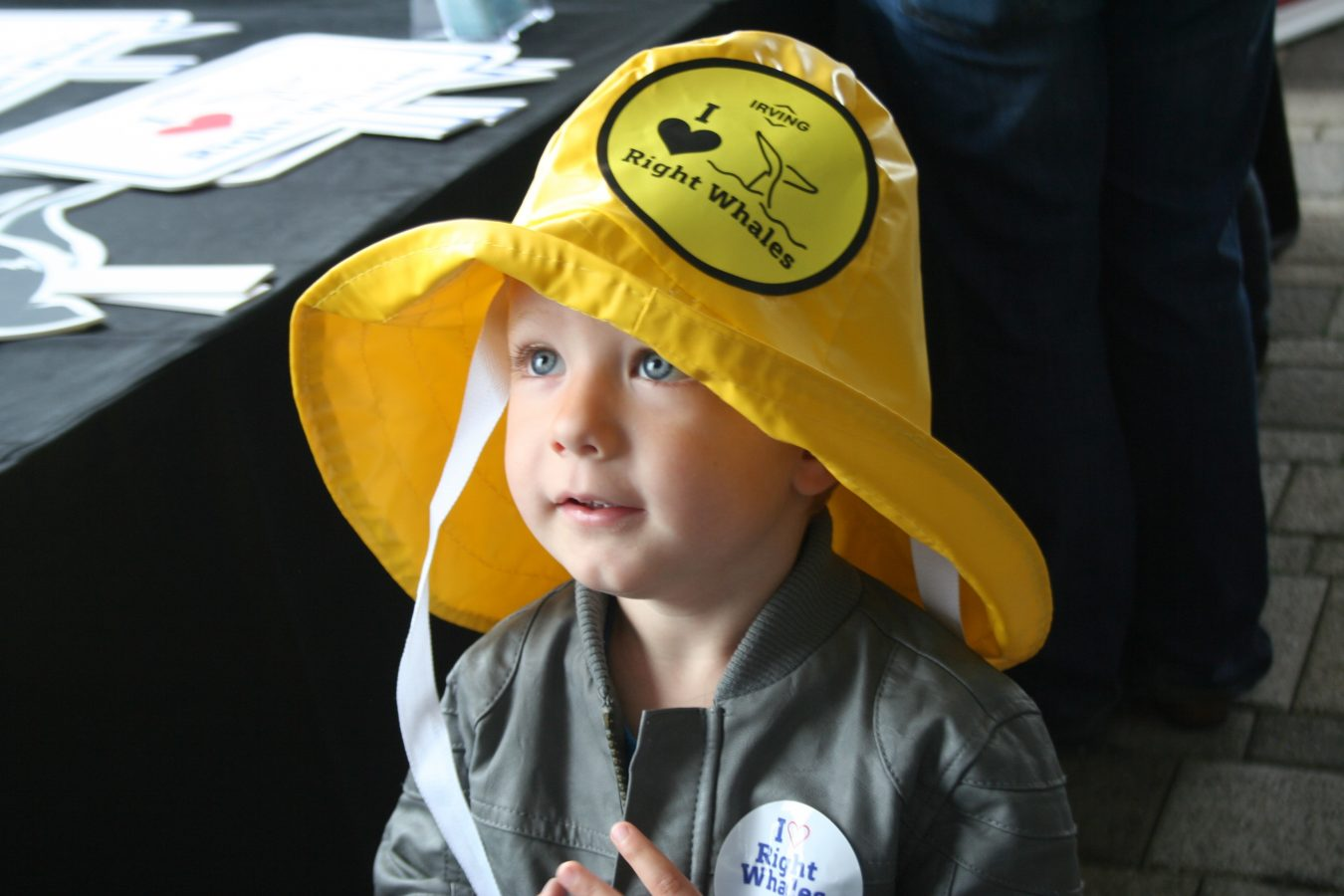 A child tries on a fisherman's hat at the 2018 New England Right Whale Festival.