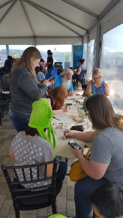A World Oceans Day 2018 visitor decorates a tote bag in the members activity Make-A-Bag, Take-A-Bag.