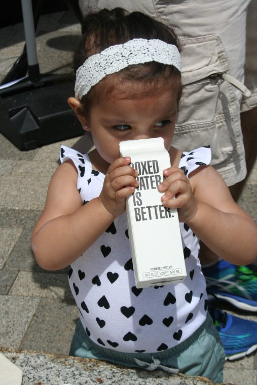 A World Oceans Day 2018 visitor tries a sample of Boxed Water.