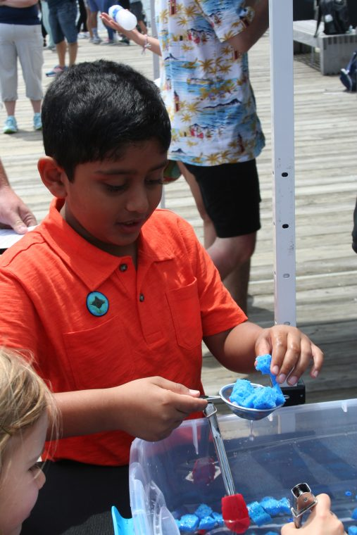 A World Oceans Day 2018 visitor simulates cleaning the oceans.