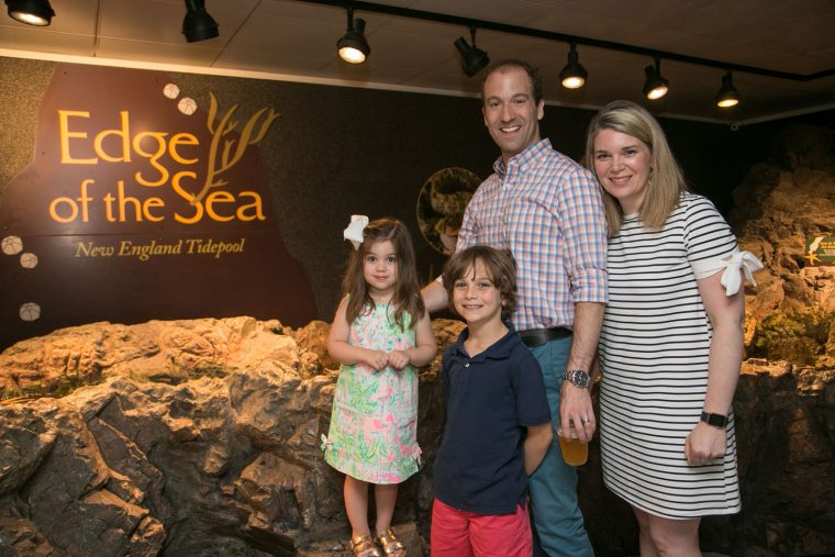 family at tidepool touch tank