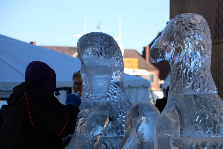An ice sculptor attaches an icy wing to the penguin.