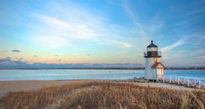 a pristine new england beach with a lighthouse against a setting sun