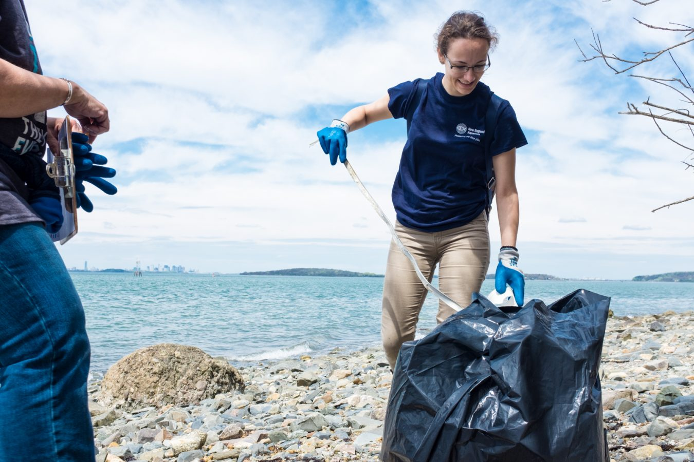 live blue Service Corps volunteer picks up trash on Grape Island