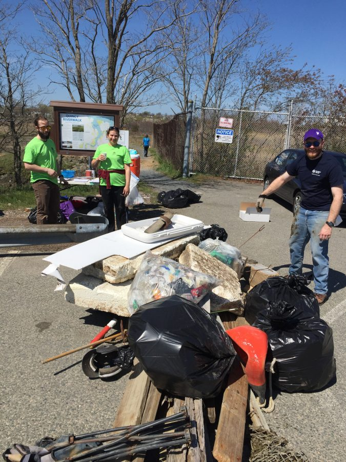a volunteer shows off a load a trash picked up during a cleanup event.
