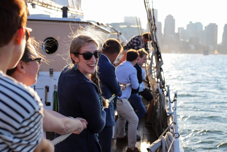 woman helps raise the sail during Cruise with The Tide 2019