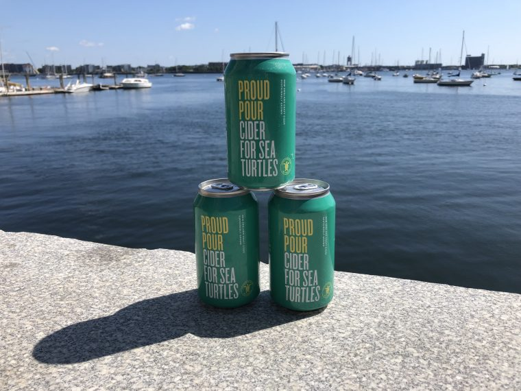 cans of Proud Pour cider in front of Boston Harbor