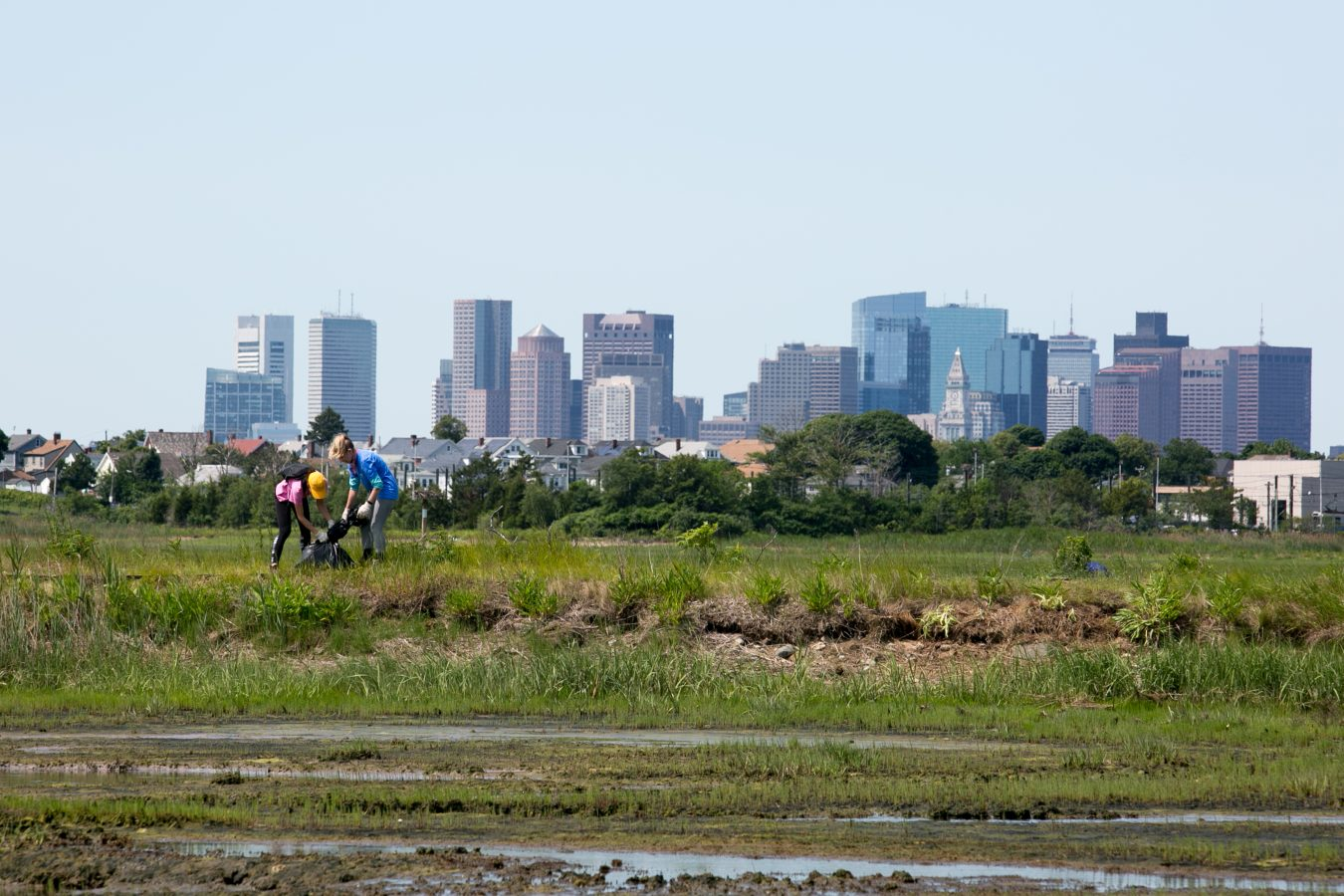 two people pick up trash at Belle Isle Reservation with the Boston skyline in the background.
